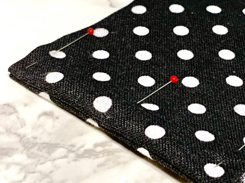 縫い目が両端にくるよう整え、ずれないように待ち針で留めます