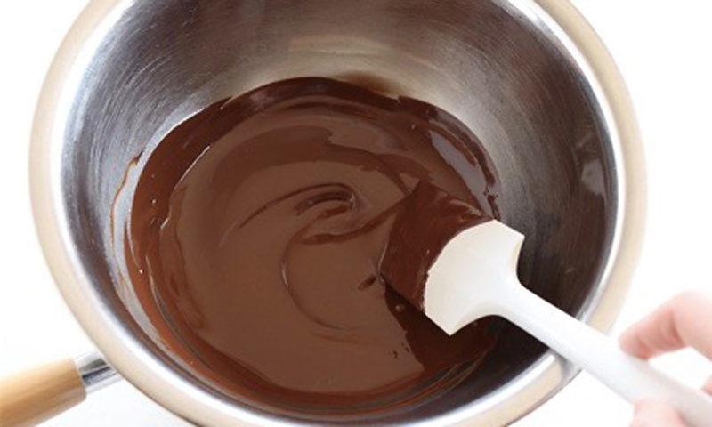 刻んだビターチョコレートをボウルに入れて湯せんにかけ、溶けてきたらゴムベラでゆっくりと混ぜながら溶かします