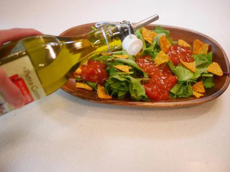グリーンサラダにトマトソース、オリーブオイルをかける