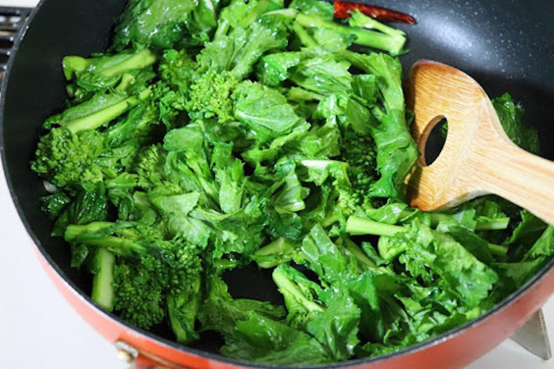 香りが出てきたら、中火にして菜の花を加えて炒め合わせます
