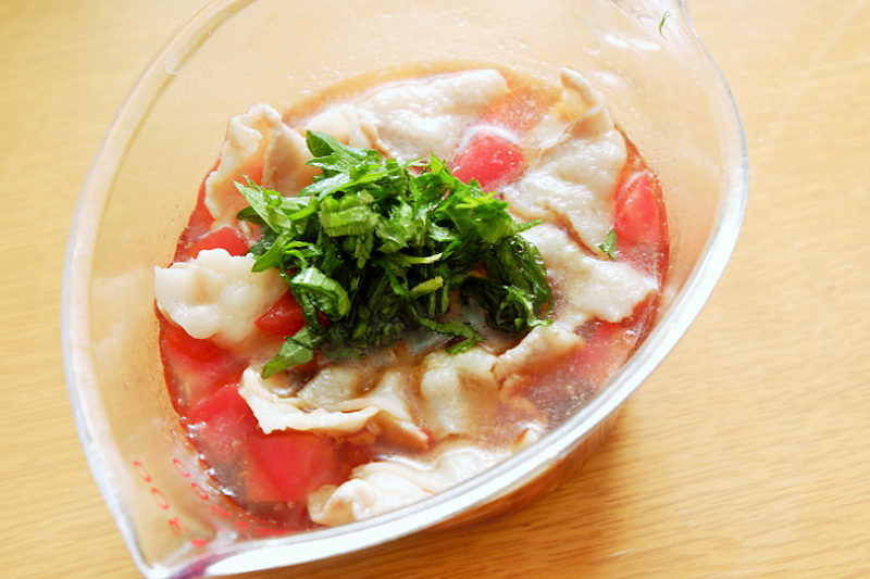 容器に豚肉、トマトを入れ、めんつゆ、水を加え、大葉をのせる