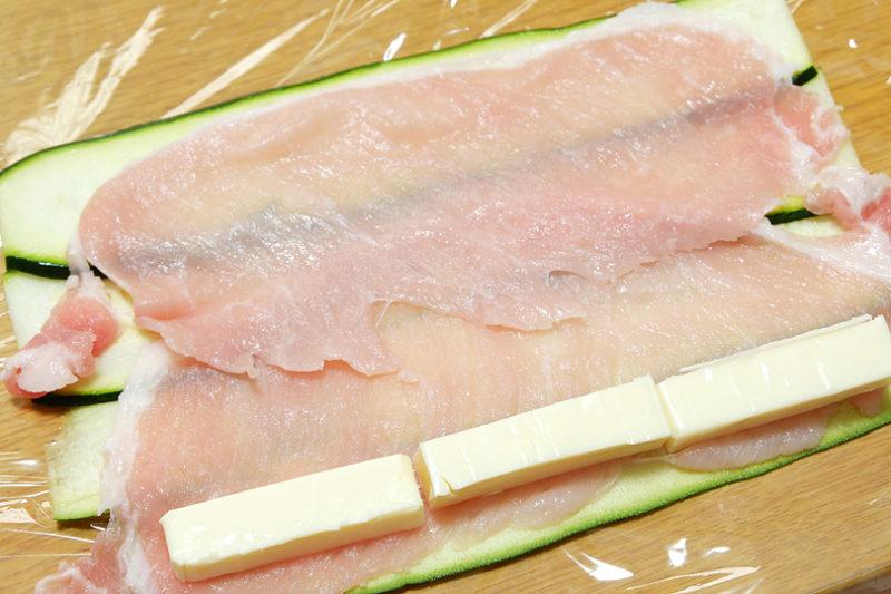 ラップの上に薄く剥いたズッキーニを並べ、その上に豚ロース肉をのせる