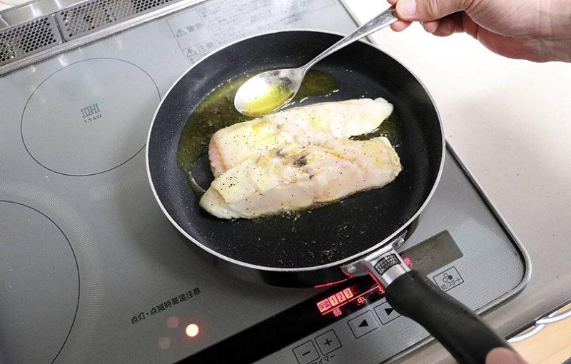 フライパンを傾け、オリーブオイルをスプーンですくって身にかける