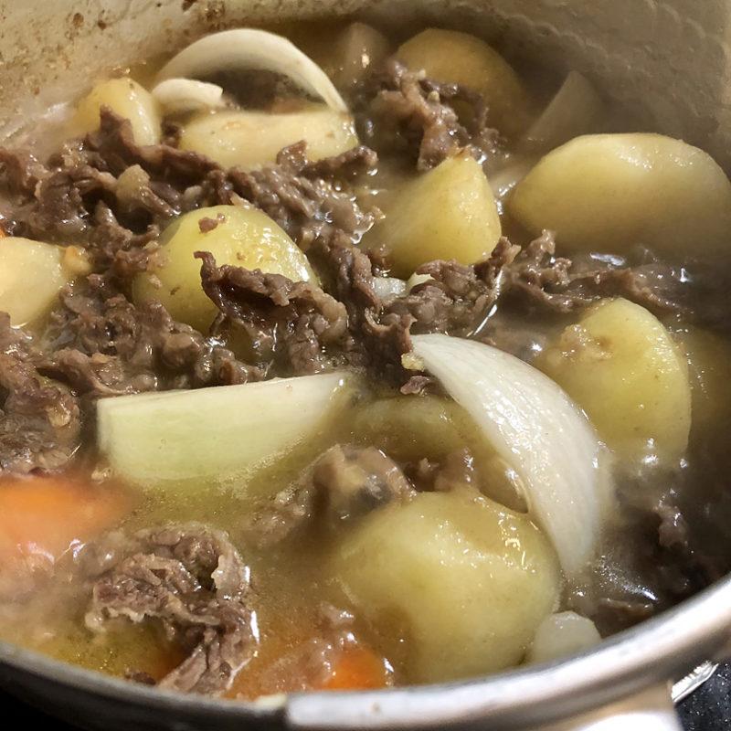 じゃがいもの表面が透き通ってきたら牛肉、にんじん、玉ねぎ、糸こんにゃく、トマトを加えて更に炒めます