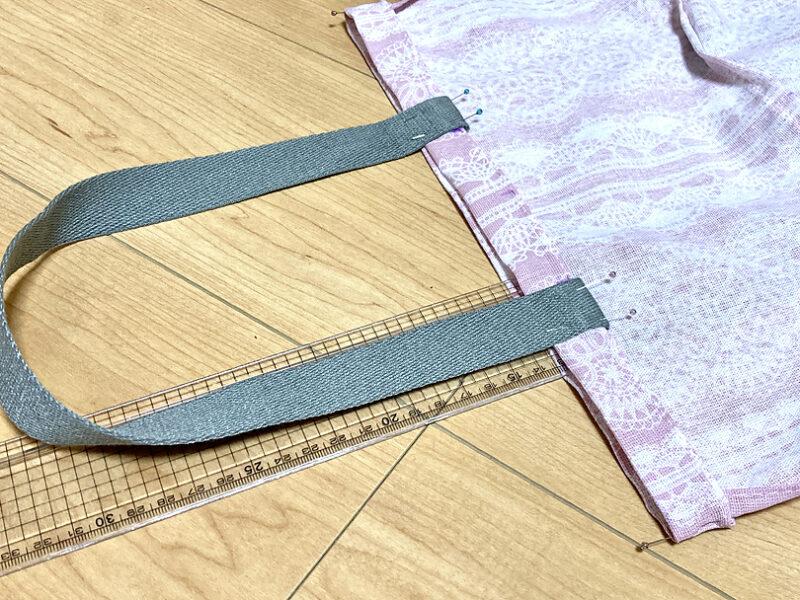間に定規など硬いものを挟むと下の布まですくうことなく待ち針を打つことができます